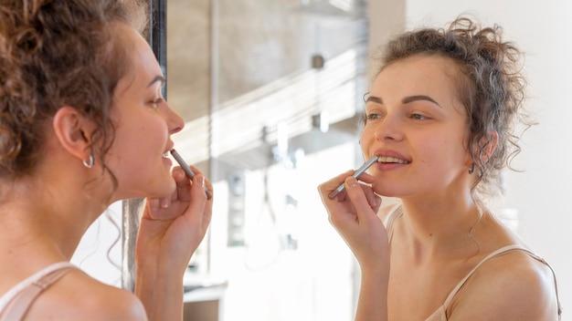 Vrouw die in spiegel kijkt en lippenstift toepast