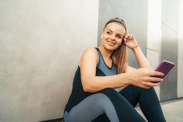 Vrouw die in sportkleding met smartphone rust
