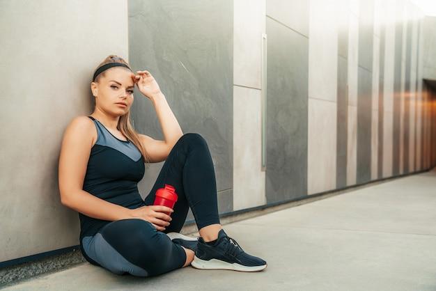 Vrouw die in sportkleding rust