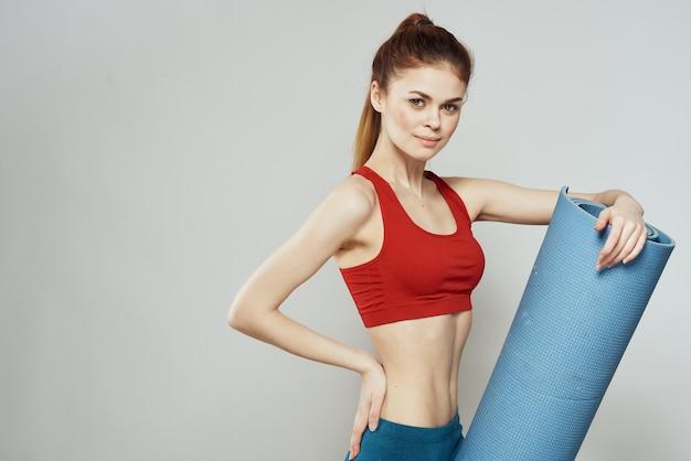 Vrouw die in sportkleding yogamat houdt