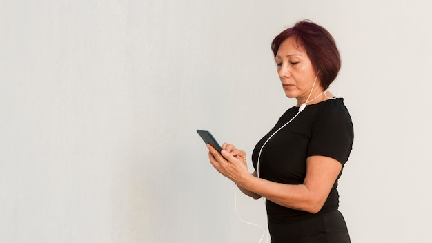 Vrouw die in sportkleren haar telefoon bekijkt