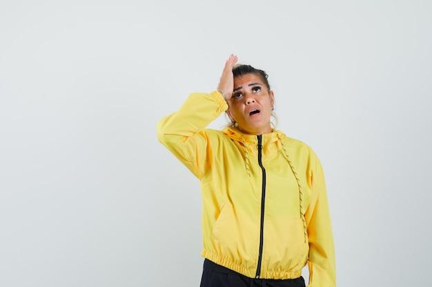 Vrouw die in sportkostuum hand aan hoofd houdt en vergeetachtig, vooraanzicht kijkt.