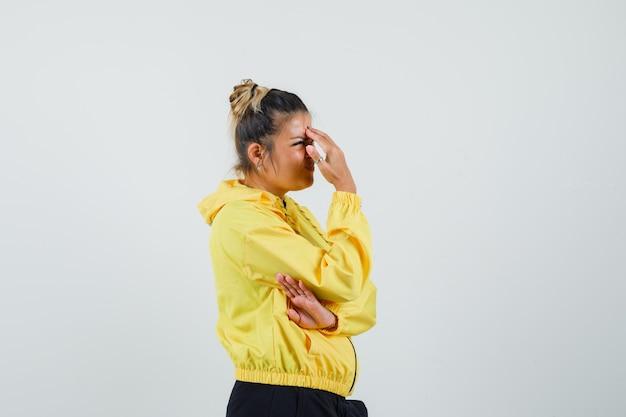 Vrouw die in sportkostuum vingers op voorhoofd houdt en vergeetachtig kijkt.