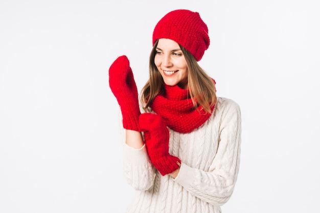 Vrouw die in sweater handschoenen aanzet