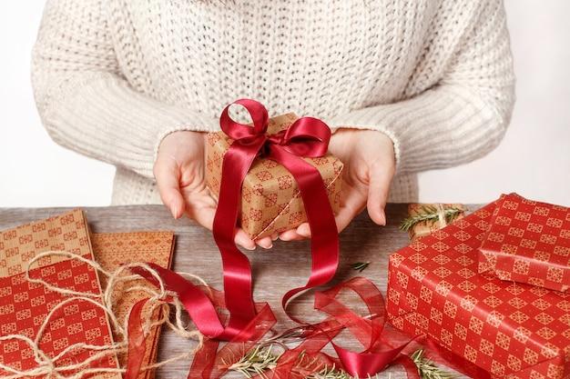 Vrouw die in sweater verpakte giften in handen houdt