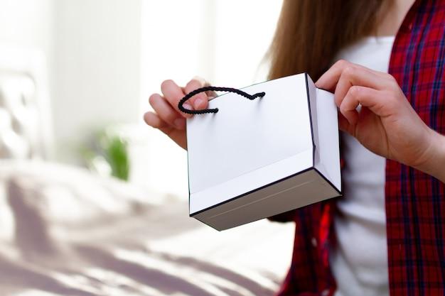 Vrouw die in t-shirt een document giftzak thuis houdt. zelf aankopen doen en geschenken ontvangen van dierbaren