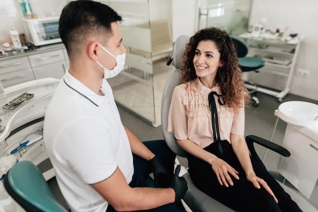 Vrouw die in tandartsbureau glimlacht