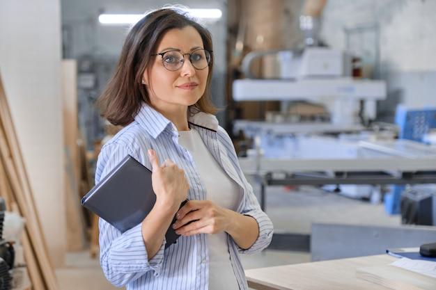 Vrouw die in timmerwerk, industrieel portret werkt. vrouw in houtbewerking workshop