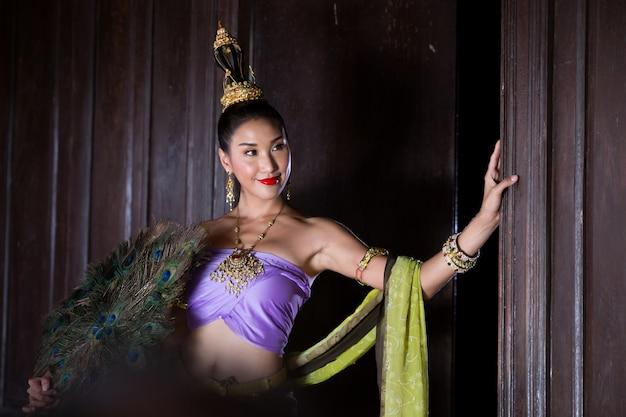 Vrouw die in traditioneel kostuum weg terwijl status tegen deur kijkt