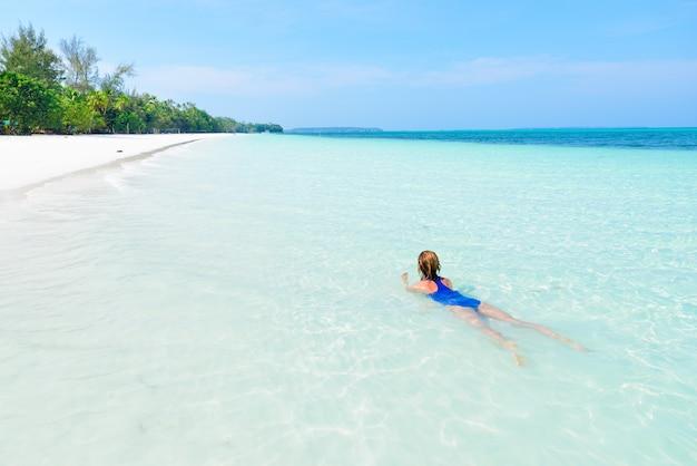 Vrouw die in tropisch strand zwemt