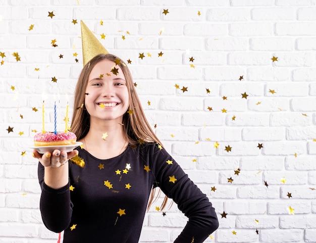 Vrouw die in verjaardagshoed een doughnut met kaarsen met gouden confettien houdt die rond vallen