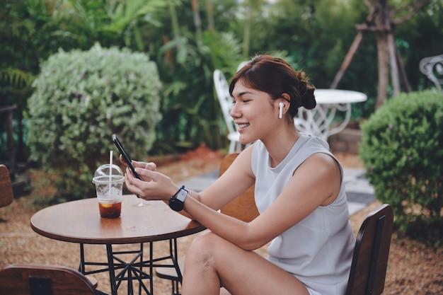 Vrouw die in videochat praat via digitale mobie en airpod white wireless terwijl ze zit