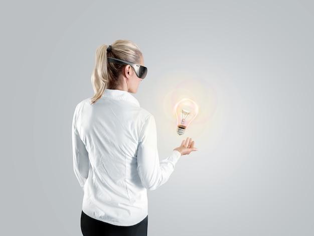 Vrouw die in virtuele werkelijkheidsglazen aan het geïsoleerde hologram kijkt