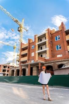 Vrouw die in volle lengte blauwdruk, bouwwerf bekijkt