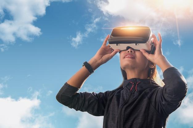 Vrouw die in vr-hoofdtelefoon omhoog in virtuele werkelijkheid kijkt. vr is een computertechnologie die een fysieke aanwezigheid simuleert en de gebruiker in staat stelt om te communiceren met de omgeving.