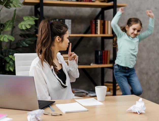 Vrouw die in vrede wil werken terwijl haar dochter lawaai maakt