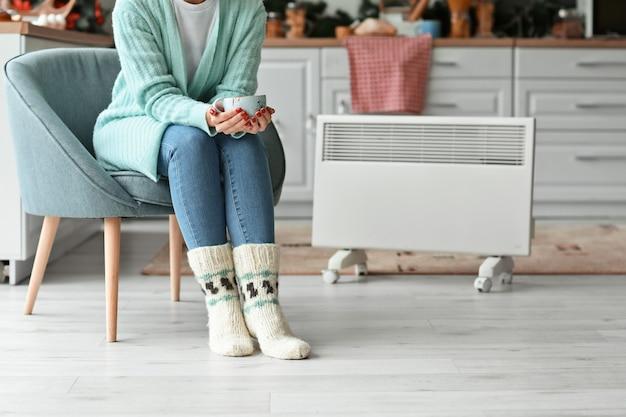 Vrouw die in warme kleren thuis hete thee drinkt. concept van het stookseizoen Premium Foto