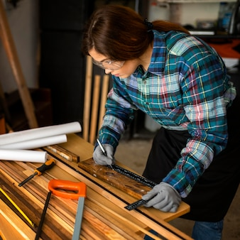 Vrouw die in werkplaats met maatregelenband werkt