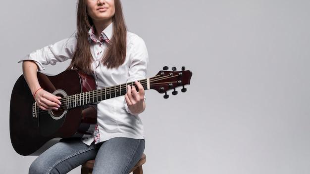 Vrouw die in wit overhemd de gitaar speelt