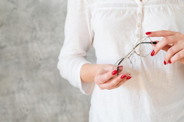 Vrouw die in wit overhemd eenvoudige oogglazen houdt. stijlvolle brillen en leeshobby