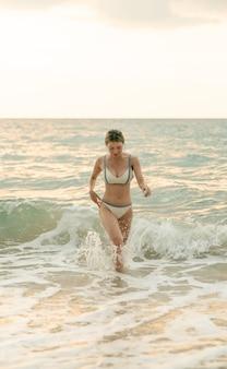 Vrouw die in witte bikini op zandstrand met zonsondergang loopt. vrouw in badkleding lopen op het zand op grote golven.