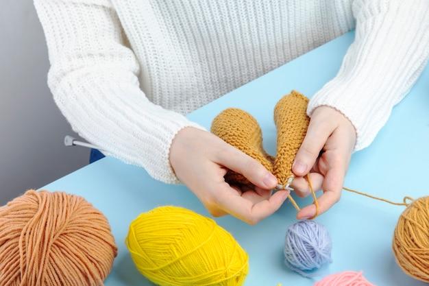 Vrouw die in witte sweater gele garenkleren breien