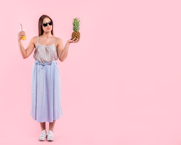 Vrouw die in zonnebril glas sap en ananas houdt