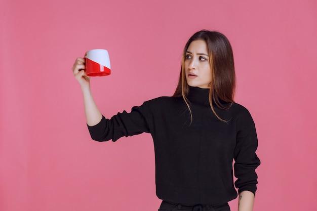 Vrouw die in zwart overhemd een koffiekop houdt en glimlacht.