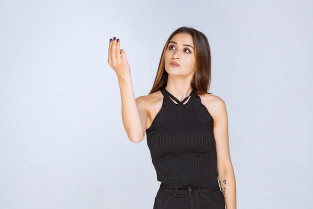 Vrouw die in zwart overhemd naar iets in haar hand kijkt.