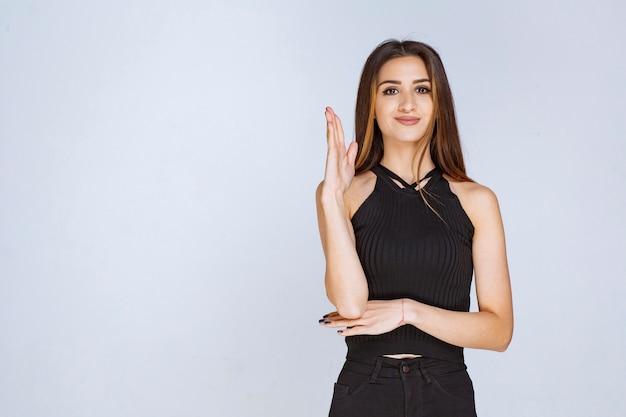 Vrouw die in zwart overhemd om aandacht vraagt.