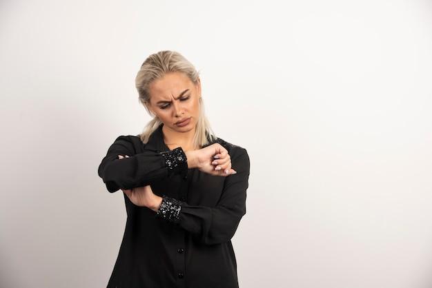 Vrouw die in zwart overhemd op haar horloge op witte achtergrond kijkt. hoge kwaliteit foto