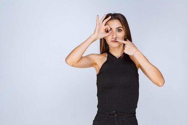 Vrouw die in zwart overhemd positief handteken maakt.