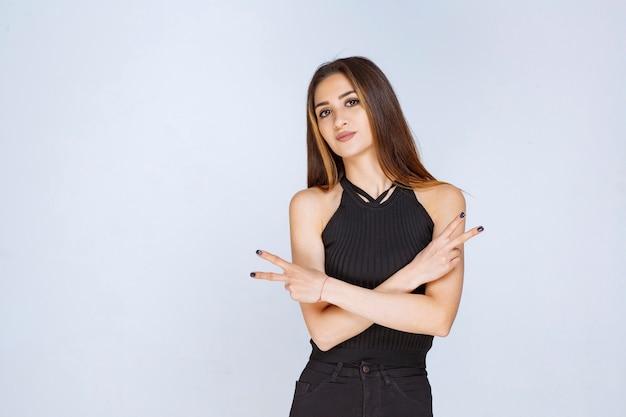 Vrouw die in zwart overhemd vredesteken maakt.