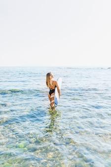 Vrouw die in zwempak met surfplank in blauwe overzees loopt