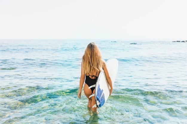 Vrouw die in zwempak met surfplank in overzees loopt