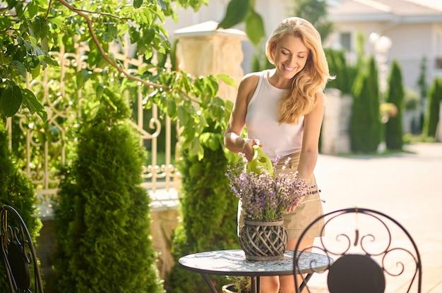 Vrouw die ingemaakte bloemen op tafel buiten water geeft