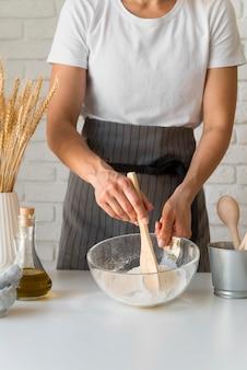 Vrouw die ingrediënten in kom mengt