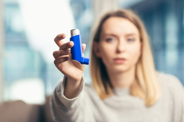 Vrouw die inhalator gebruikt terwijl ze thuis aan astma lijdt