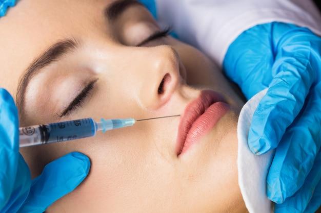 Vrouw die injectie op haar lippen ontvangt