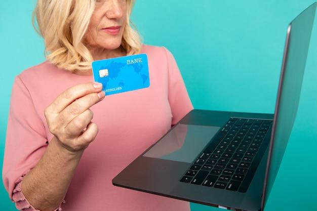 Vrouw die internet gebruikt om online te winkelen met computer en creditcard.