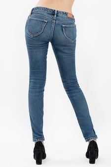 Vrouw die jeans dragen die die achterkant zijaanzicht half-lengte stellen op witte achtergrond wordt geïsoleerd