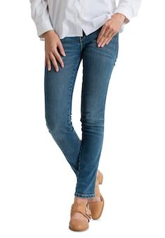 Vrouw die jeans en wit overhemd met benen draagt die in vooraanzicht halve lengte worden gekruist die op witte achtergrond wordt geïsoleerd