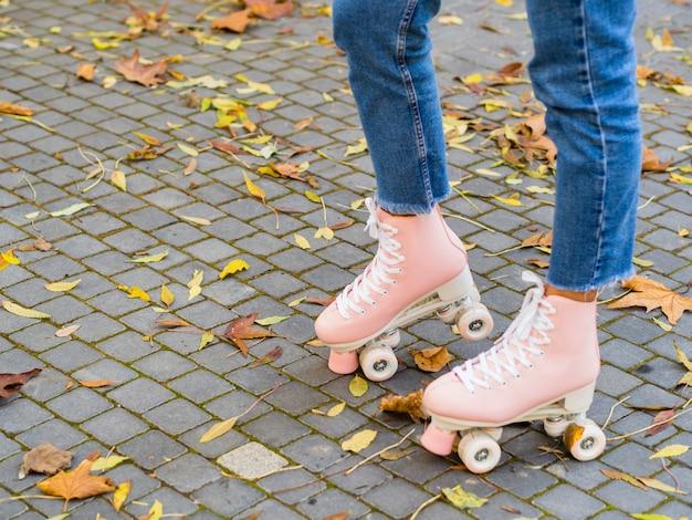 Vrouw die jeans met rolschaatsen en exemplaarruimte draagt