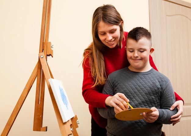 Vrouw die jongen met benedensyndroomverf helpt