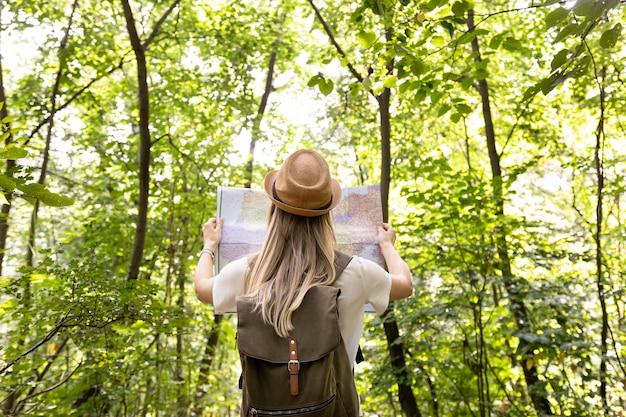 Vrouw die kaart erachter bekijkt van