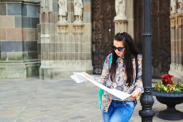Vrouw die kaart onderzoekt dichtbij het oude gebouw bij stadsstraat. toeristische vrouw wandelen in de oude stad.