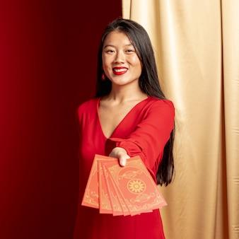 Vrouw die kaarten voor chinees nieuw jaar tonen
