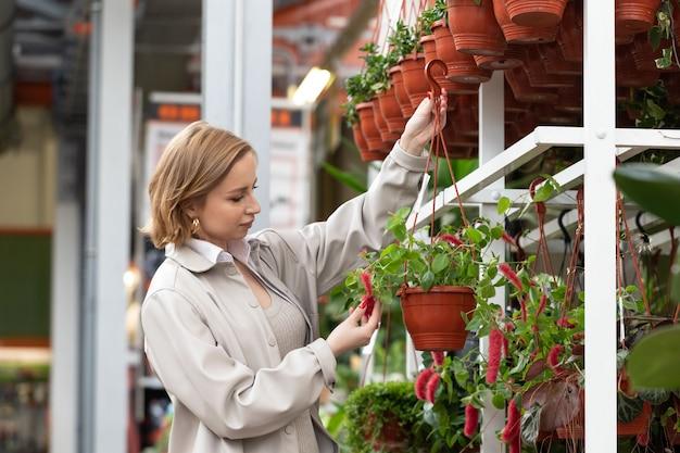 Vrouw die kamerplant in tuincentrum kiest, raakt installatie met haar hand, die hangende bloempotten houdt