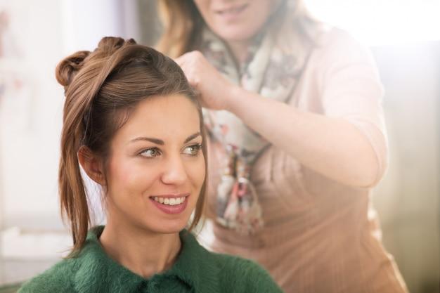 Vrouw die kapsel klaar krijgen bij schoonheidssalon