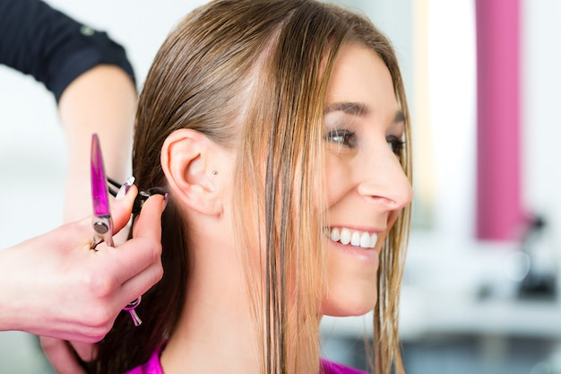 Vrouw die kapsel ontvangt van herenkapper of kapper